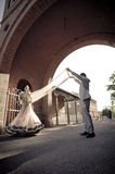 Young attractive Indian couple dancing under brick archway Stock Photos