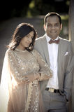 Young attractive Indian couple standing together outdoors. In formal attire Stock Images