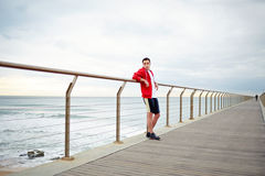 Young attractive jogger stands on the pier leaning on the rail. Morning jogging, fitnes and healthily lifestyle, sport and healthy concept royalty free stock image