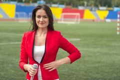 Young attractive journalist is reporting from the stadium Stock Images