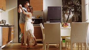Young attractive joyful couple have fun kissing dancing while cooking in the kitchen at home . 3840x2160 stock video