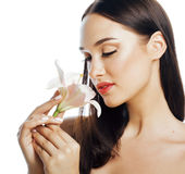 Young attractive lady close up with hands on face isolated flower lily brunette spa nude makeup Royalty Free Stock Image