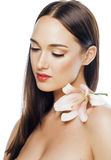 Young attractive lady close up with hands on face isolated flower lily brunette spa nude makeup Royalty Free Stock Photography