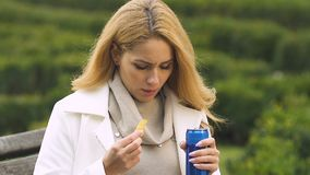 Young attractive lady eating snacks and drinking carbonated beverage, obesity. Stock footage stock video