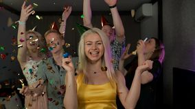 Young attractive lady at great confetti birthday party. Great confetti birthday party in flat apartment suit. Young attractive handsome female and her friends stock video footage