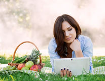 Young attractive lady lying in the park with a tablet Stock Photos