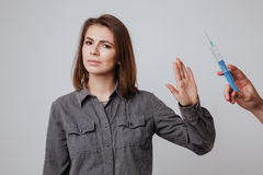 Young attractive lady make stop gesture to syringe. Stock Image