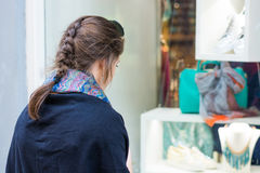 Young and attractive lady window shopping. Deciding what to buy. Customer in shopping street royalty free stock photo