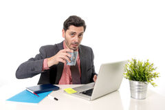 Young attractive Latin businessman working at office computer desk drinking cup of coffee Royalty Free Stock Photos