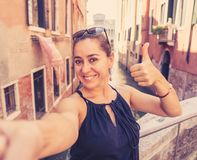 Woman tourist smiling and showing thumb up while taking a selfie at the canal in Venice Italy stock image