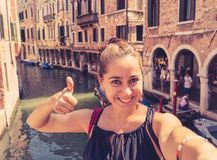 Woman tourist smiling and showing thumb up while taking a selfie at the canal in Venice Italy stock photo