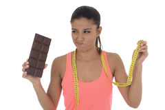 Young attractive latin woman holding taylor measure tape and chocolate bar in healthy nutrition diet Stock Photo