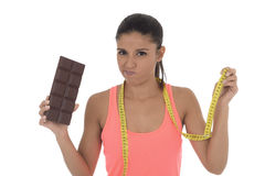 Young attractive latin woman holding taylor measure tape and chocolate bar in healthy nutrition diet Royalty Free Stock Photography