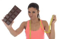 Young attractive latin woman holding taylor measure tape and chocolate bar in healthy nutrition diet Royalty Free Stock Images