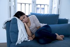 Young attractive latin woman lying at home couch worried suffering depression feeling sad and desperate. Young attractive latin woman lying at home living room Royalty Free Stock Images