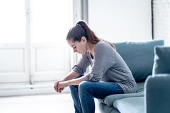 Young woman suffering from depression feeling sad and lonely on sofa at home. Young attractive latin woman lying at home living room couch feeling sad tired and royalty free stock image