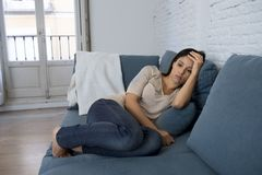 Young attractive latin woman lying at home couch worried suffering depression feeling sad and desperate. Young attractive latin woman lying at home living room Royalty Free Stock Photos