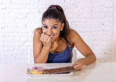 Young attractive latin woman sitting at table about to eat chocolate and doughnuts looking excited and happy in no more diet, suga stock photo