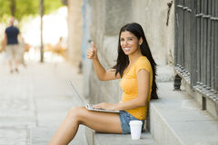Young attractive latin woman in trendy casual clothes studying or working on laptop computer. In urban background giving thumb up Royalty Free Stock Photo