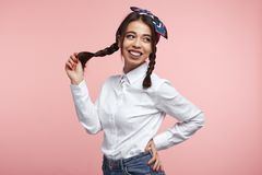 Cheerful latina female with bright smile, wearing white shirt and bandana on head, holding her ponytail against pink wall. Young attractive latina hispanic girl royalty free stock image