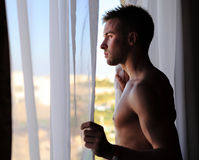 Young attractive macho looking in window Stock Photos