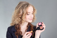 Young attractive make up artist with brush over grey Royalty Free Stock Photos