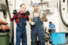 Car Technicians At Work. Young attractive male automobile mechanic and his beaded colleague in workwear standing in service garage and discussing work Stock Photo