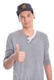 Young attractive male teenager with thumb up isolated on white. Stock Photo