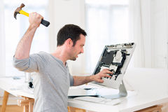 Young attractive man angry against computer Royalty Free Stock Images