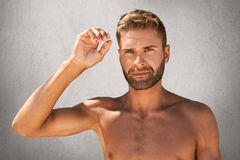 Young attractive man with appealing appearance standing naked, raising his hand, showing his biceps. Stylish macho man posing agai stock photos
