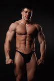 Young attractive man in a black bathing suit bodybuilder Royalty Free Stock Photo