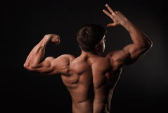 Young attractive man in a black bathing suit bodybuilder. With relief muscles Stock Photography