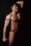 Young attractive man in a black bathing suit bodybuilder. With relief muscles Stock Photos