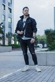 Young attractive man in black jeans jacket standing on cityscape background. royalty free stock images