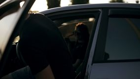 Young attractive man in black T shirt and sunglasses get in car, dark silver sedan and ready to go with her girlfriend. From the parking lot stock video