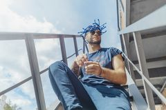 Young attractive man with blue dreadlocks sitting on staircase and shaking his hair. royalty free stock photography