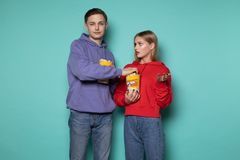 Young attractive man in blue hoodie stealing popcorn from his girlfriend, beautiful blonde girl looks at him indignantly stock images