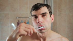 Young attractive man brushing his teeth looking in the mirror. Guy brushing his teeth with a toothbrush. care for the