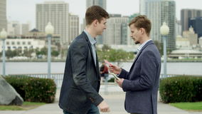 Young attractive man is buying a credit card on a sidewalk in Coronado. Young bearded guy is standing on a sidewalk with his money and waiting for another guy stock footage