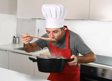 Young attractive man in chef hat and red cook apron testing flavor. While cooking soup holding pot with steam at modern home kitchen royalty free stock photo