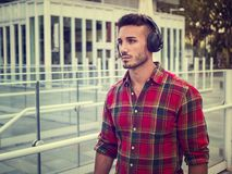 Young man in city setting with headphones royalty free stock images