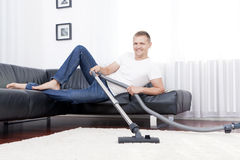 Young attractive man is cleaning vacuum on carpet. Royalty Free Stock Photos