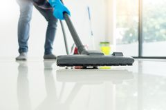 Young attractive man is cleaning vacuum commercial cleaning equi. Pment on floor at home helping wife stock photos