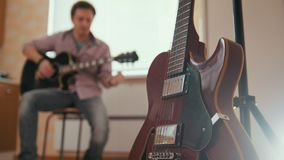 Young attractive man composes music on the guitar and plays, other musical instrument in the foreground, blurred concept. Young attractive man composes music on stock video