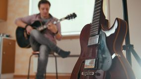Young attractive man composes music on the guitar and plays, other musical instrument in the foreground, blurred. Young attractive man composes music on the stock video footage