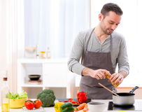 Young attractive man cooking in a kitchen Royalty Free Stock Image