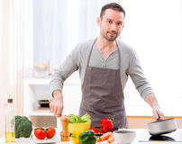 Young attractive man cooking in a kitchen Royalty Free Stock Images