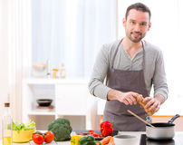 Young attractive man cooking in a kitchen Stock Image