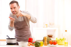 Young attractive man cooking in a kitchen Stock Photography