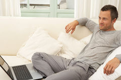 Young attractive man on couch with laptop at home. Royalty Free Stock Photography